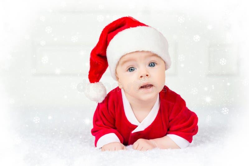 Grappige Kerstmisbaby in Santa Claus-kostuum die op witte achtergrond liggen stock foto