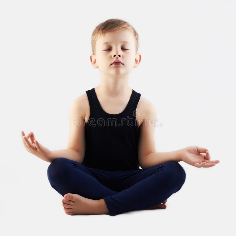 Grappige kind het praktizeren yoga weinig Jongen doet yoga stock afbeelding