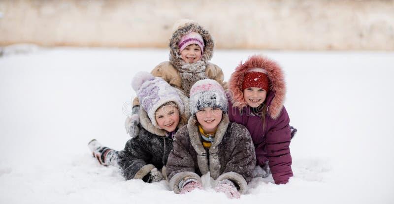 Grappige kinderen die en op sneeuw de winterpark spelen lachen stock foto