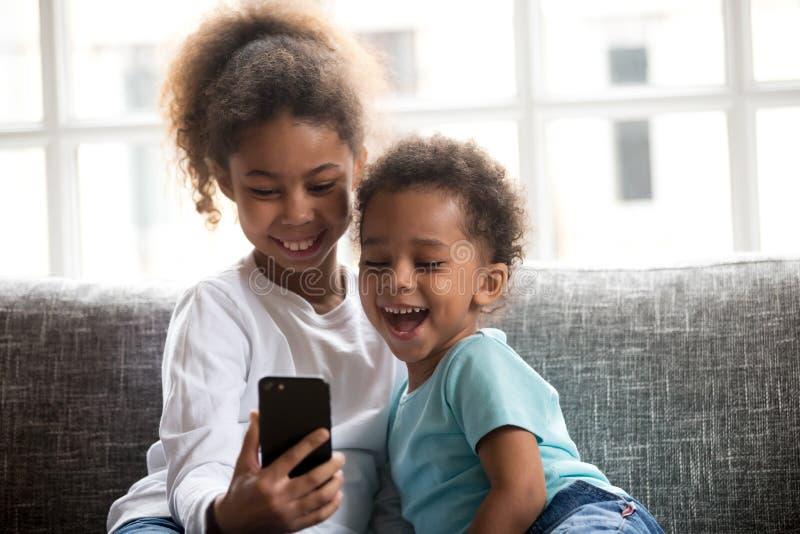 2 grappige kinderen die smartphone het letten op video gebruiken die op cou lachen royalty-vrije stock foto
