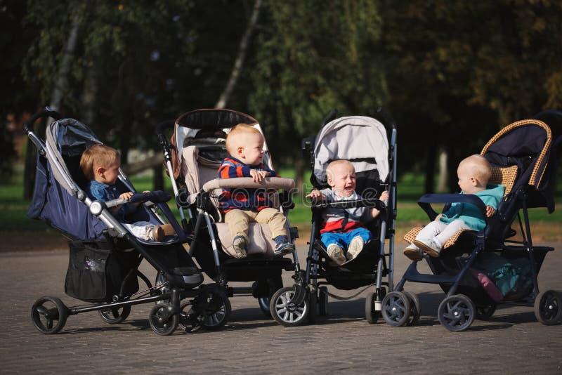 Grappige kinderen die in wandelwagens in park zitten stock foto
