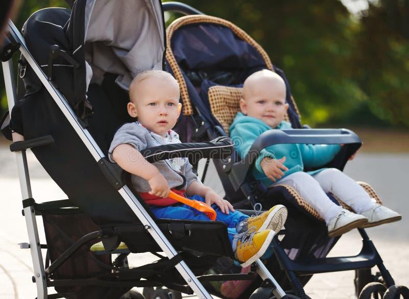 Grappige kinderen die in wandelwagens in park zitten royalty-vrije stock fotografie