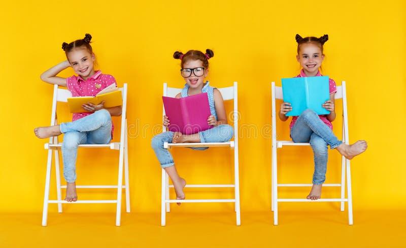 Grappige kinderenmeisjes gelezen boeken op een gekleurde gele achtergrond royalty-vrije stock afbeelding