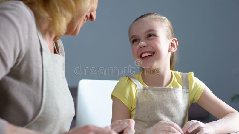 Grappige kleindochter en haar grootmoeder die terwijl het koken bij keuken lachen royalty-vrije stock foto