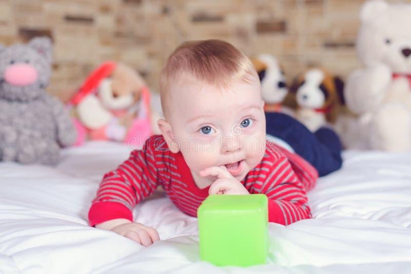 Grappige kleine babyjongen die buik het glimlachen liggen royalty-vrije stock fotografie