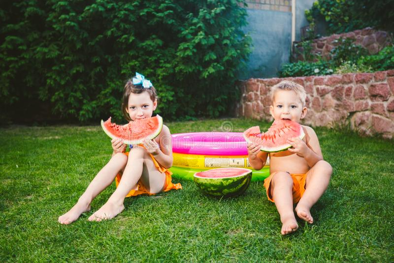 Grappige kleine jonge geitjesbroer en zuster die watermeloen op groen gras thuis eten dichtbij opblaasbare pool in yard De jongen royalty-vrije stock afbeeldingen
