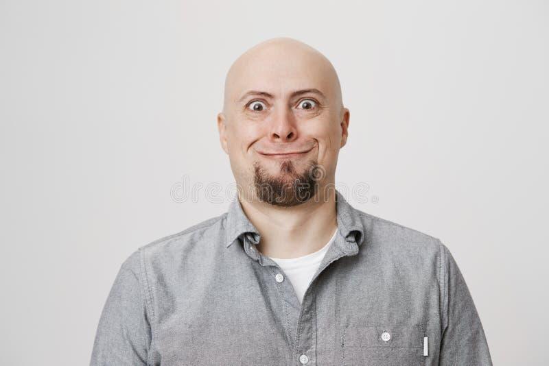Grappige knappe kale Kaukasische mens die met baard en bizarre glimlach met geknalde ogen bij camera staren terwijl status over g stock foto's
