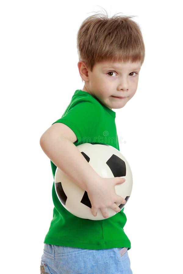 Grappige leuk weinig jongen in een groene t-shirt en jeans royalty-vrije stock afbeelding