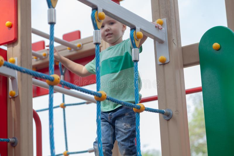 Grappige leuke de jongensspelen van de blondebaby op de speelplaats De emotie van geluk, pret, vreugde stock fotografie