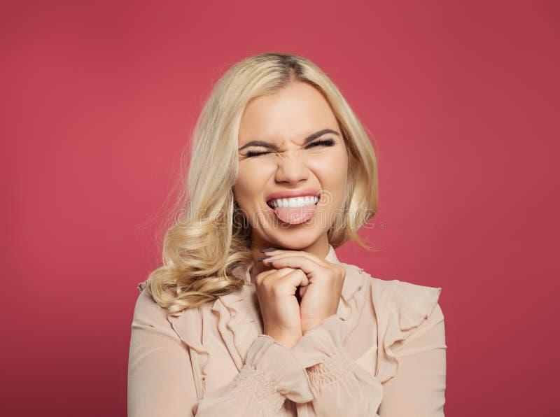 Grappige leuke jonge vrouw die, en tong over roze achtergrond tonen glimlachen knipogen Het portret van de vrouwentong uit royalty-vrije stock afbeelding
