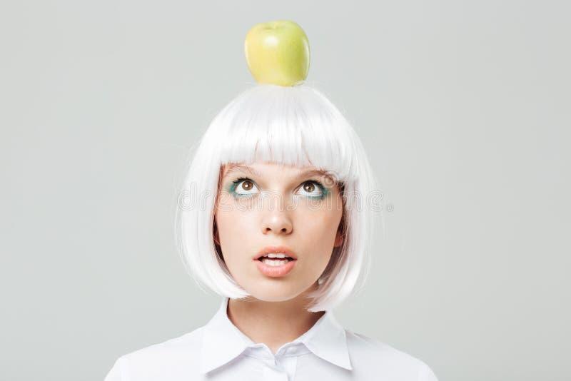 Grappige leuke jonge vrouw met appel op haar hoofd stock fotografie