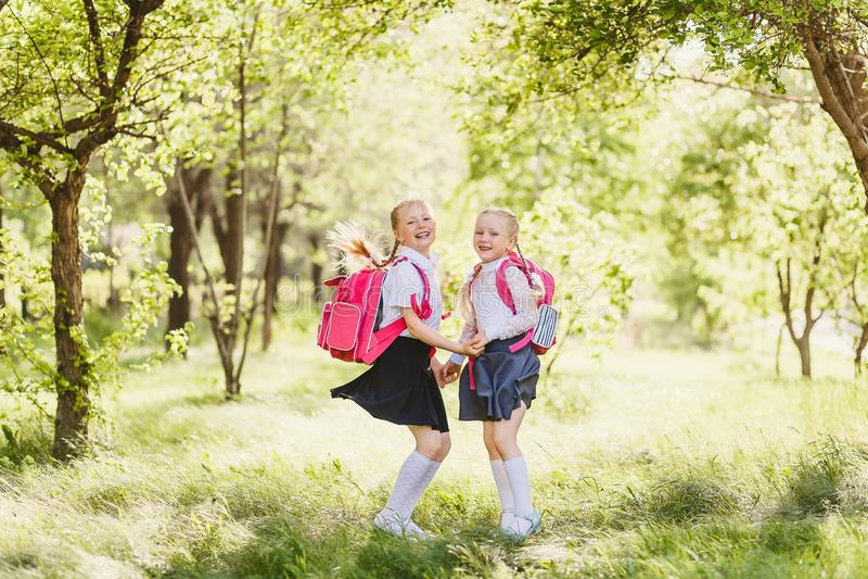 Grappige leuke meisjes in eenvormige school en met rugzakken royalty-vrije stock afbeelding
