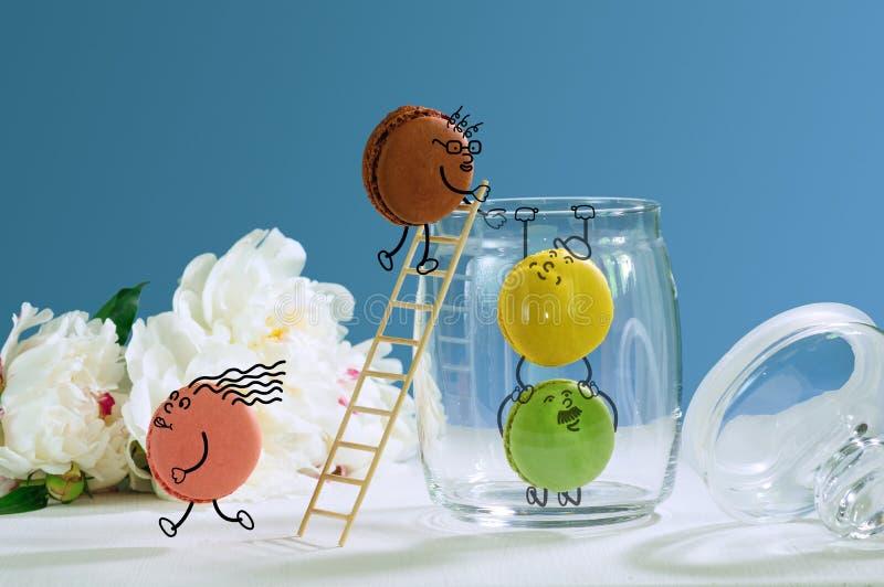Grappige macarons die van kruik voor snoepjes proberen te ontsnappen stock foto's