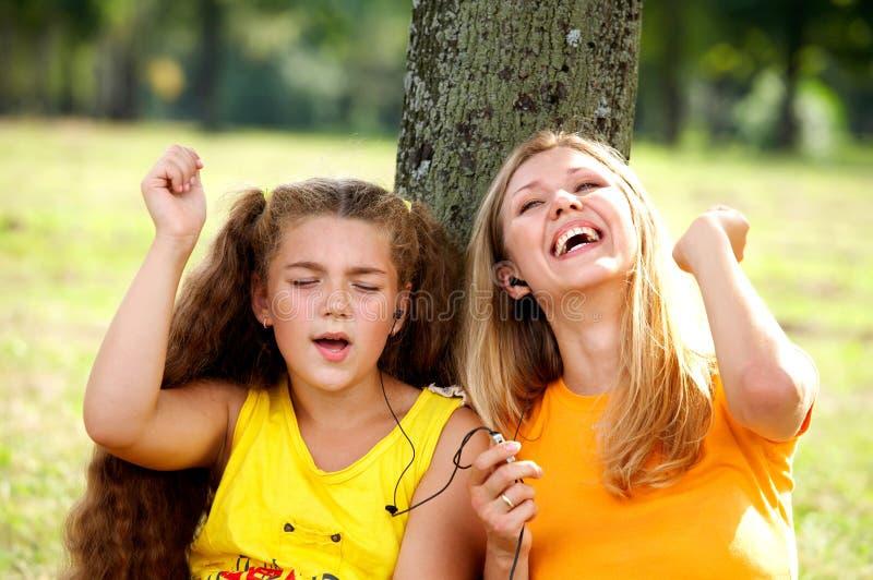 Grappige mamma en dochter het luisteren muziek stock foto's