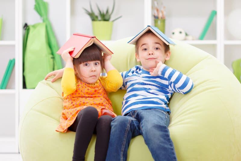 Grappige meisje en jongen die hun hoofden behandelen stock afbeelding