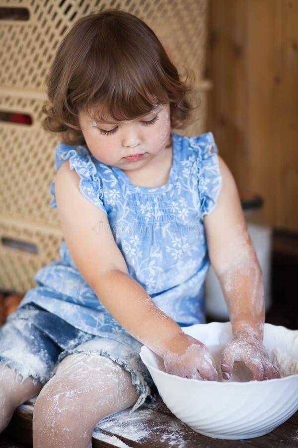 Grappige meisje kokende pastei in keuken, het kneden deeg stock foto's
