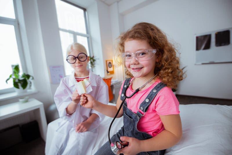 Grappige meisjes die glazen dragen die glazen na samen het spelen eten stock foto