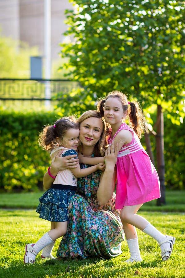Grappige meisjes die op het gazon met haar moeder lopen De zusters spelen samen met mamma Moeder Zorg Gelukkige Familie royalty-vrije stock afbeeldingen