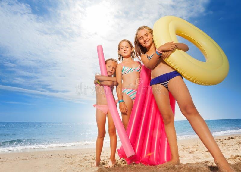Grappige meisjes met kleurrijke zwemmende hulpmiddelen op strand stock fotografie