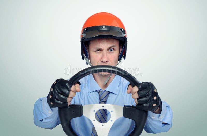 Grappige mens in een rode helm met stuurwiel, het concept van de autobestuurder royalty-vrije stock afbeelding