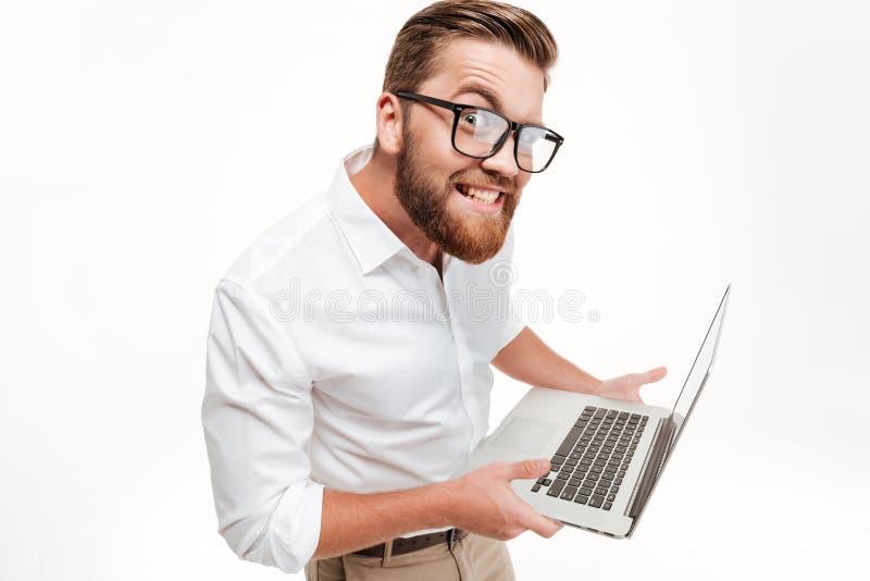 Grappige mens in oogglazen die laptop houden en bij camera staren royalty-vrije stock fotografie