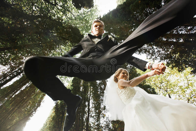 Grappige modieuze jonge bruid en bruidegom op de achtergrondlente su royalty-vrije stock fotografie