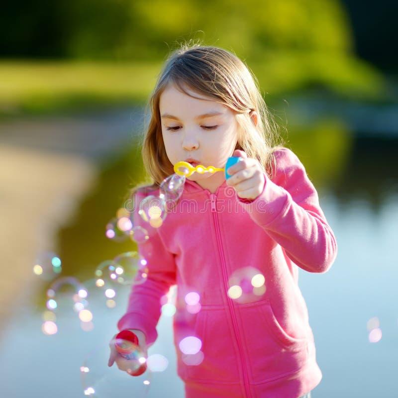 Grappige mooie meisje blazende zeepbels stock fotografie