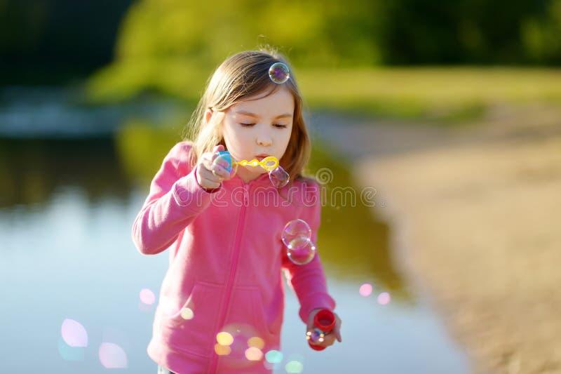 Grappige mooie meisje blazende zeepbels stock afbeelding