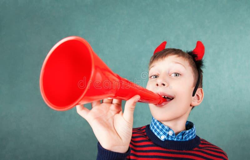 Grappige ongehoorzame schooljongen die het rode pijp glimlachen spelen royalty-vrije stock foto's