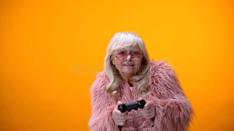 Grappige oude vrouw met bedieningshendel die videospelletje, hobby en vrije tijd beweren te spelen stock fotografie