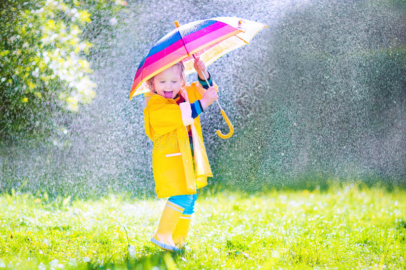 Grappige peuter met paraplu het spelen in de regen royalty-vrije stock afbeeldingen