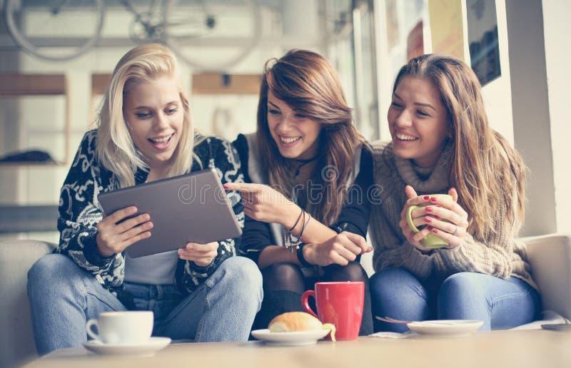 Grappige post Drie beste vrienden die digitale tablet samen gebruiken royalty-vrije stock foto's