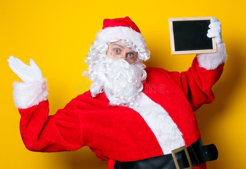Grappige Santa Claus die zwarte raad houden stock fotografie
