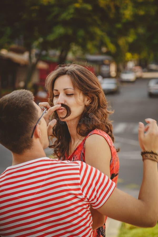 Grappige snor Mooi jong houdend van paar die valse snor van haar maken terwijl het zitten in openlucht bij groene stadsstraat, de stock fotografie