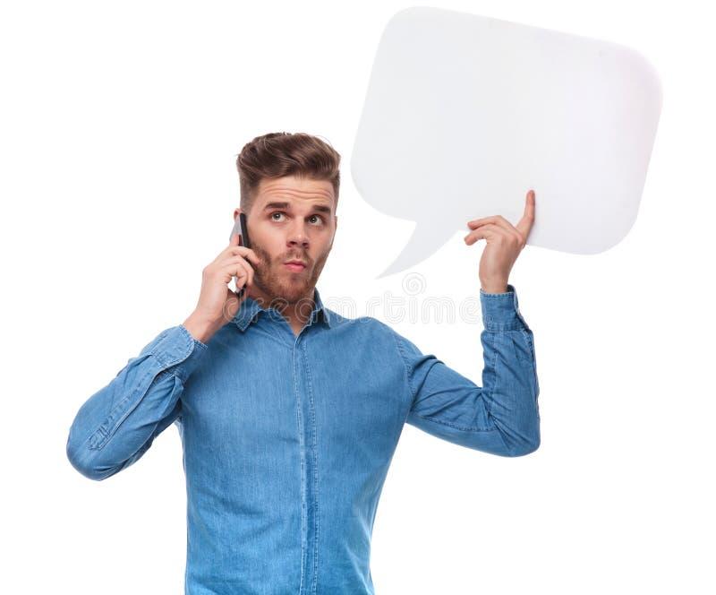 Grappige toevallige mens die met toespraakbel op de telefoon spreken stock afbeeldingen
