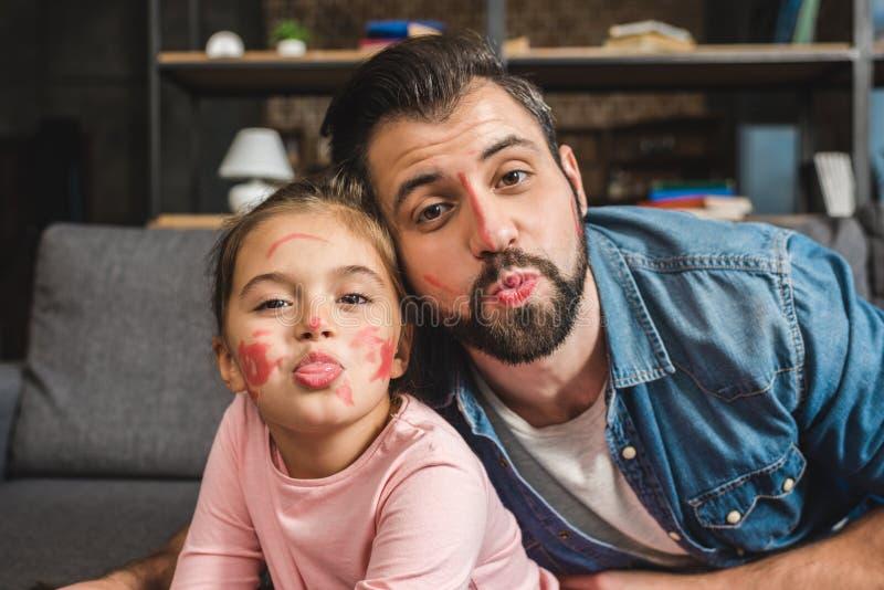 grappige vader en dochter met geschilderde gezichten die kus beweren stock afbeeldingen