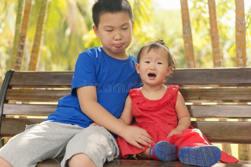 Grappige verschillende uitdrukking tussen broer en weinig zuster stock fotografie