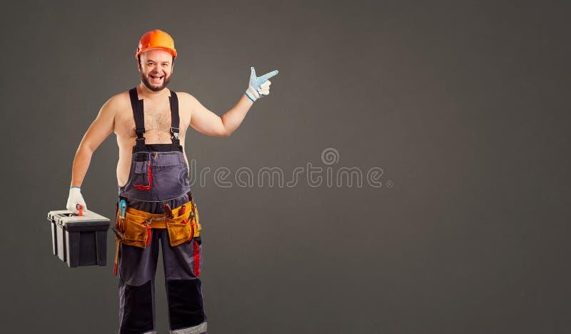 Grappige vette bouwer met de punten van een hulpmiddeldoos aan een achtergrond stock foto's