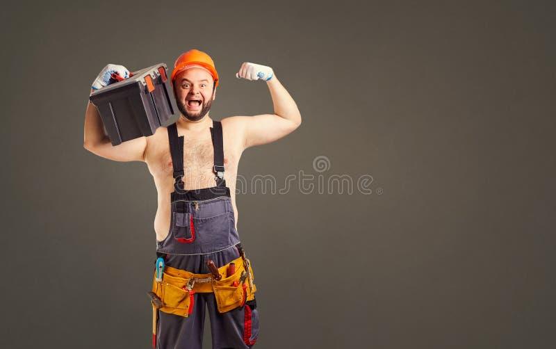 Grappige vette gebaarde bouwer met een hulpmiddeldoos stock foto