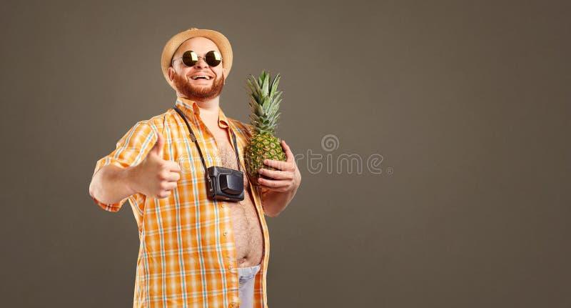 Grappige vette gebaarde mens met een ananas op vakantie royalty-vrije stock fotografie