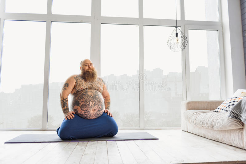 Grappige vette mens die yoga thuis doen stock foto's