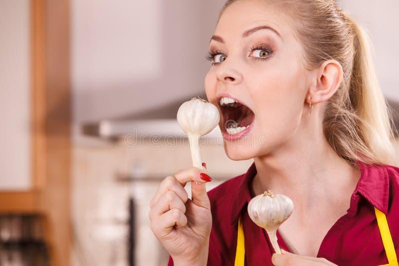 Grappige vrouw die etend knoflook bijten royalty-vrije stock afbeeldingen