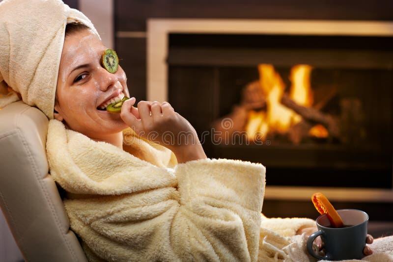 Grappige vrouw die fruit van gezichtsmasker eet stock foto's