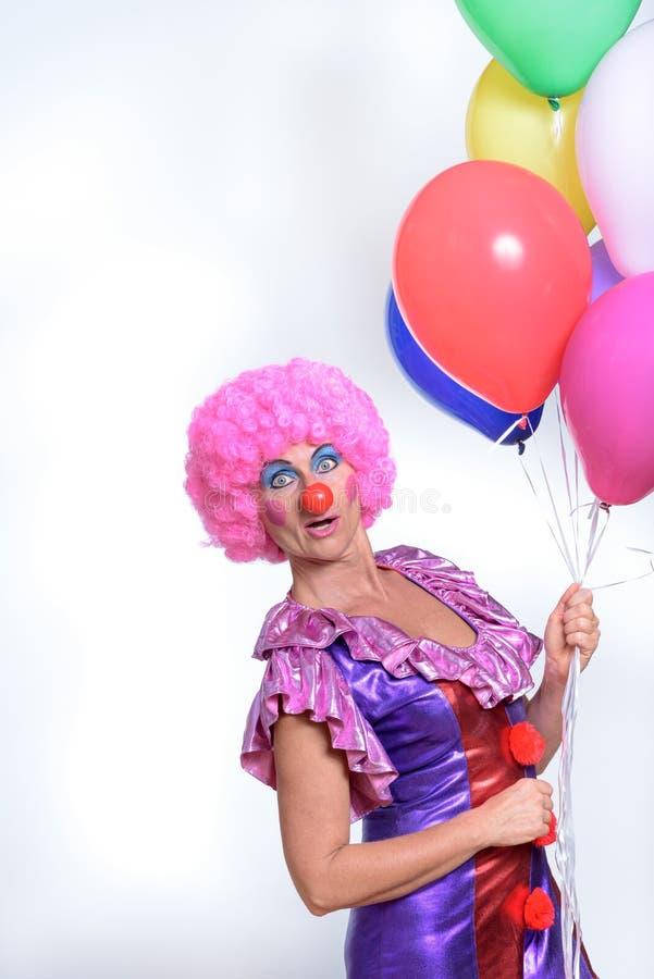 Grappige Vrouwelijke Clown Holding Colorful Balloons royalty-vrije stock afbeelding