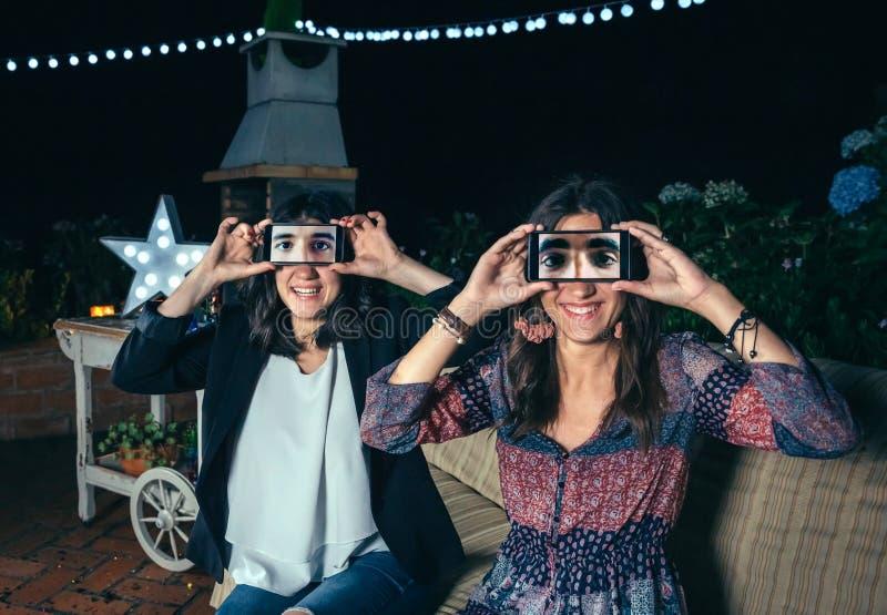 Grappige vrouwen die smartphones tonend mannelijke ogen houden stock foto's