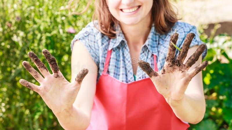 Grappige vrouwenlandbouwer die vuile handen tonen royalty-vrije stock afbeelding