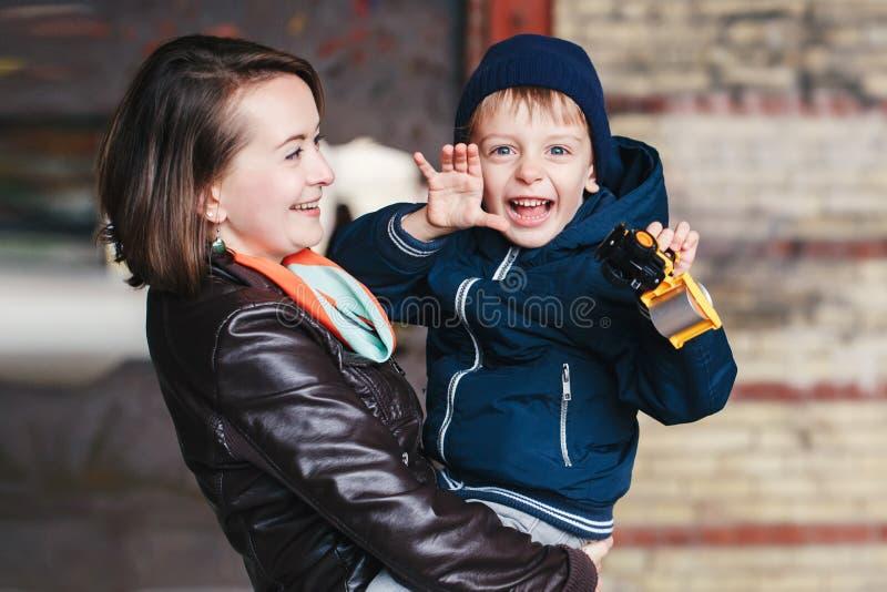 grappige witte glimlachende lachende Kaukasische moeder en zoon met stuk speelgoed, gelukkige familie van twee stock fotografie