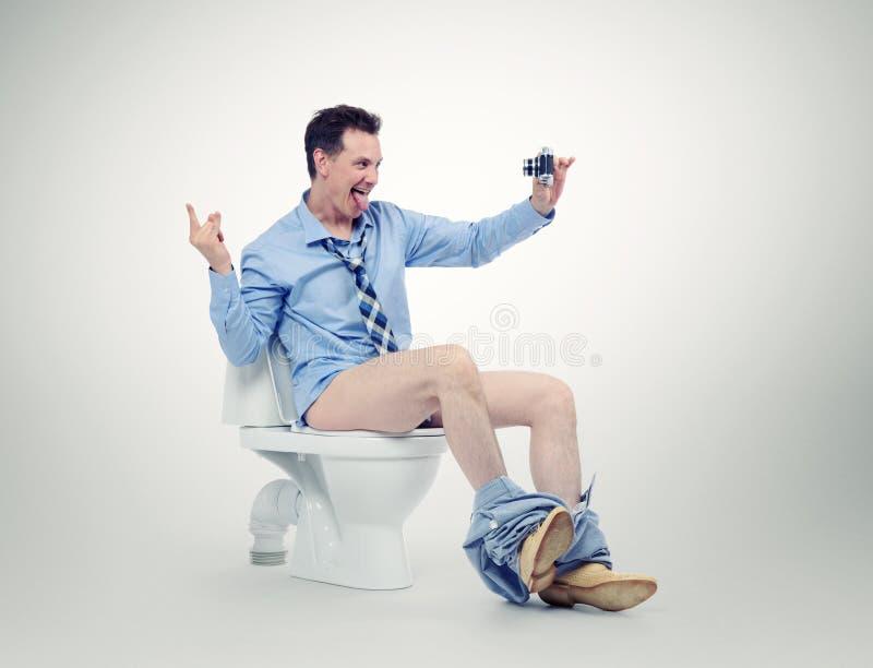 Grappige zakenman die fotograferen in het toilet stock afbeelding