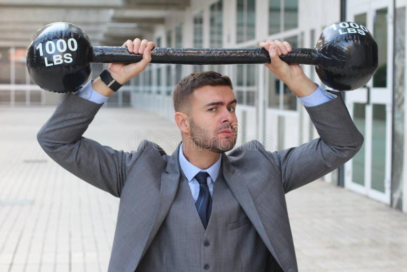 Grappige zakenman die zware gewichten opheffen royalty-vrije stock afbeeldingen