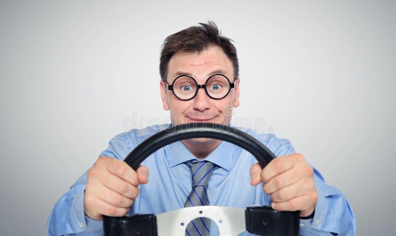Grappige zakenman in glazen met een stuurwiel stock fotografie